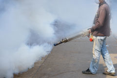 Arbeitskraft, die Abfluss am Wohngebiet mit Insektenvertilgungsmitteln zum ki einnebelt Stockbild