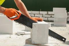 Arbeitskraft, die Ausschnitt Block mit einer Hand mit Kohlensäure durchsetzte, sah im Freien Stockfotografie