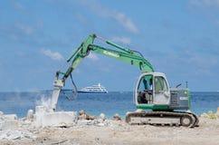 Arbeitskraft, die Bagger an der Baustelle auf Ufer von Ozean verwendet Stockfotos