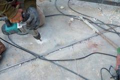 Arbeitskraft, die Bodenbohrung der elektrischen Bohrmaschine durch Werkzeugmaschine verwendet lizenzfreie stockfotos