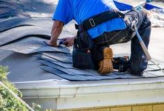 Arbeitskraft, die das Dach eines Hauses repariert Stockbilder