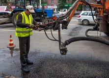 Arbeitskraft, die das Loch im Asphalt auf einer Stadtstraße unter Verwendung des flüssigen Asphaltversorgungsschlauches durch spe Lizenzfreie Stockbilder