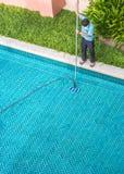 Arbeitskraft, die das Pool säubert Stockfotografie