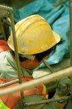 Arbeitskraft, die den Abwasserkanal hinuntergeht Stockfoto