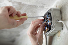 Arbeitskraft, die den elektrischen Kasten installiert Stockbild