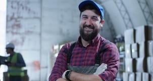 Arbeitskraft, die an der Kamera in einem Lager lächelt stock video