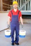 Arbeitskraft, die Eimer in einer Baustelle hält Lizenzfreies Stockfoto