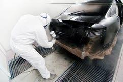 Arbeitskraft, die ein Auto in der Garage unter Verwendung eines Spritzpistolengewehrs malt Lizenzfreie Stockfotografie