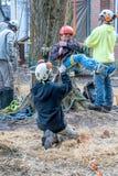 Arbeitskraft, die ein Kind in ein Baumgeschirr sichert lizenzfreies stockbild