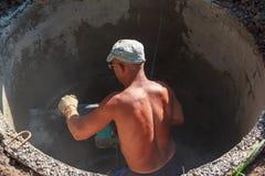 Arbeitskraft, die ein Loch mit einem Perforator für ein Rohr in einem Stahlbetonbrunnen locht Lizenzfreie Stockfotos