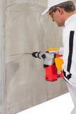 Arbeitskraft, die ein Loch mit einem Perforator macht Lizenzfreies Stockbild