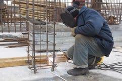 Arbeitskraft, die ein Metallgitter an schweißt Stockbild