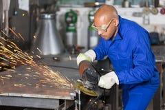 Arbeitskraft, die ein Metallstück mit Winkel gringer reibt lizenzfreies stockfoto