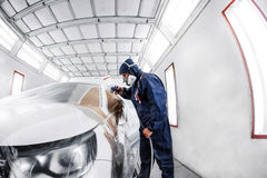 Arbeitskraft, die ein weißes Auto in der speziellen Garage, in tragendem Kostüm und in der Schutzausrüstung malt Stockbilder