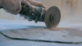 Arbeitskraft, die eine Fliese unter Verwendung eines Winkelschleifers an der Baustelle schneidet stock video
