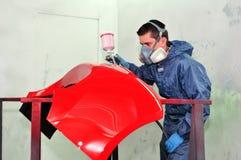 Arbeitskraft, die eine Schutzvorrichtung malt. Stockbild