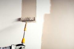 Arbeitskraft, die eine Wand, malend mit Pinseldekoration auf Innenwänden vergipst stockfoto