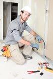 Arbeitskraft, die einen Draht schneidet Stockbilder