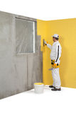 Arbeitskraft, die einen Gips auf einer Eckewand verbreitet Stockbild