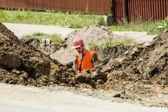 Arbeitskraft, die einen Graben für Abwasserkanal gräbt Stockfotografie