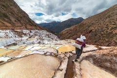 Arbeitskraft, die einen großen Sack Salz, auf den terassenförmig angelegten Salzpfannen in Maras, Urubamba-Tal, Peru trägt Manuel Stockbilder