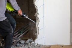 Arbeitskraft, die einen Jackhammer verwendet, um in Wand zu bohren lizenzfreies stockfoto