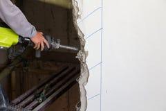 Arbeitskraft, die einen Jackhammer verwendet, um in Wand zu bohren stockbilder