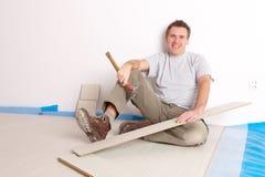 Arbeitskraft, die einen lamellierten Bodenbelag installiert Stockfotografie
