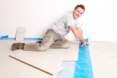 Arbeitskraft, die einen lamellierten Bodenbelag installiert Stockbild