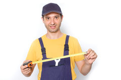 Arbeitskraft, die einen Maßband lokalisiert auf Weiß hält Stockfotos