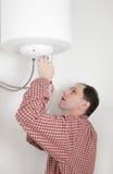 Arbeitskraft, die einen Warmwasserbereiter installiert Lizenzfreies Stockbild