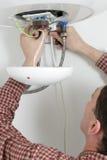 Arbeitskraft, die einen Warmwasserbereiter installiert Stockbilder