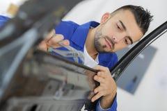 Arbeitskraft, die Fahrzeugkarosserie kontrolliert stockfotografie
