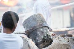 Arbeitskraft, die flüssiges Metall zum Werfen von Buddha-Statue gießt lizenzfreie stockbilder