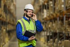 Arbeitskraft, die am Handy am Lager spricht Lizenzfreies Stockfoto