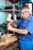 Arbeitskraft, die Holz mit einem Meißel und einem Hammer schnitzt Lizenzfreies Stockfoto
