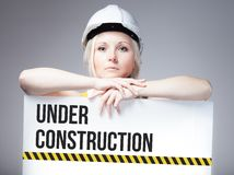 Arbeitskraft, die im Bau Zeichen auf Informationsbrett hält Lizenzfreies Stockfoto