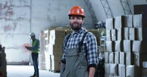 Arbeitskraft, die in Kamera in einem Lager lächelt stock footage