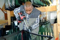 Arbeitskraft, die Kleber auf Glas setzt lizenzfreie stockfotos