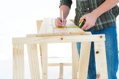 Arbeitskraft, die Maßband verwendet, um auf hölzerner Planke zu markieren Stockbild