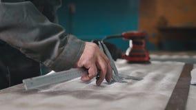 Arbeitskraft, die Maße und Kennzeichen auf dem Metallteil unter Verwendung eines Tasterzirkels macht lizenzfreies stockbild