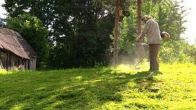 Arbeitskraft, die manuell grünes Gras mit Treibstoff L trimmt Stockbild
