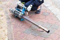 Arbeitskraft, die Maschine vorbereitet, um mit Insektenvertilgungsmitteln einzunebeln, um Aedes zu töten Lizenzfreie Stockfotografie