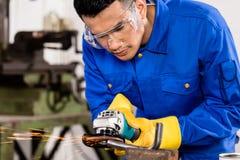 Arbeitskraft, die an Metall mit Schleiferwerkzeug arbeitet lizenzfreies stockbild