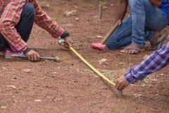 Arbeitskraft, die mit messendem Band, Hammer und Nagel arbeitet Lizenzfreies Stockbild