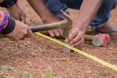 Arbeitskraft, die mit messendem Band, Hammer und Nagel arbeitet Stockbilder