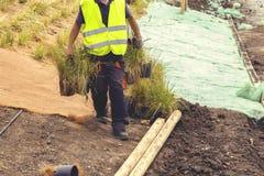 Arbeitskraft, die neues Gras für das Pflanzen 2 vorbereitet Lizenzfreie Stockbilder