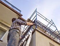 Arbeitskraft, die oben die Strichleiter geht stockbild