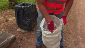 Arbeitskraft, die Plastikflaschen in der Tasche sortiert stock footage