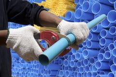 Arbeitskraft, die PVC-Rohr schneidet Lizenzfreies Stockfoto